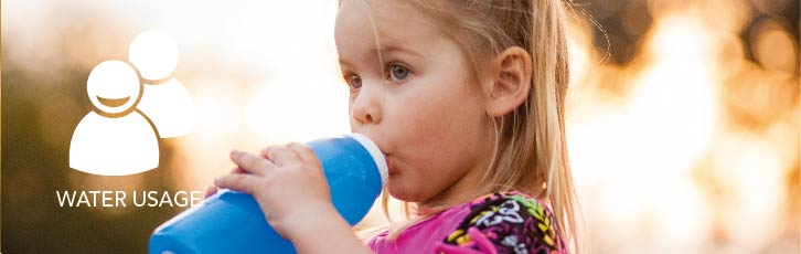 A young girl drinks from a bottle